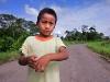 Nine-year-old Jairo Yumbo shows his birth-deformed hand on the road in front of his home in Rumipamba.